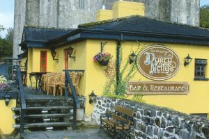 Yellow walled Irish pub with stone wall and wooden deck located next to a castle. Est. 1620.